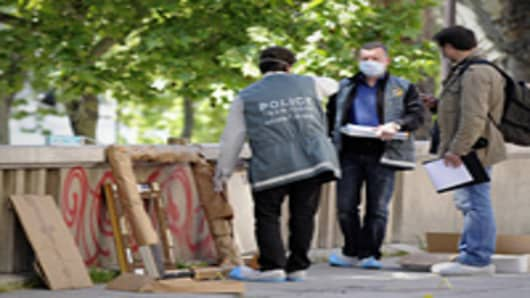 Policemen stand by painting frames outside the Paris' Musee d'Art Moderne where five works including paintings by modern masters Henri Matisse and Pablo Picasso have been stolen.