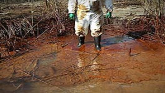 A Greenpeace activist walks on an oil-covered beach along the Gulf of Mexico on May 20, 2010 near Venice, Louisiana. Although BP says that it is capturing more of the massive oil leak, thousands of barrels continue gushing into the Gulf south of the Louisiana coast.