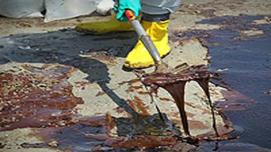 A BP cleanup crew shovels oil from a beach on May 24, 2010 at Port Fourchon, Louisiana. BP CEO Tony Hayward, who visited the beach, said that BP is doing everything possible to clean up the massive oil spill still gushing into the Gulf of Mexico.