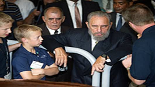 Cuban President Fidel Castro talk with Cliff Kaehler, 13, Seth Kaehler, 11, and their father Ralph Kaehler, through an interpreter as they show him livestock from their Minnesota farm during the U.S. Food & Agribuisiness Exhibition September 26, 2002 in Havana, Cuba.
