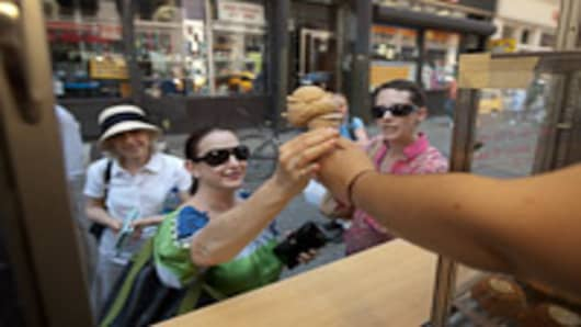 A customer orders an ice cream cone from a Van Leeuwen gourmet food truck.