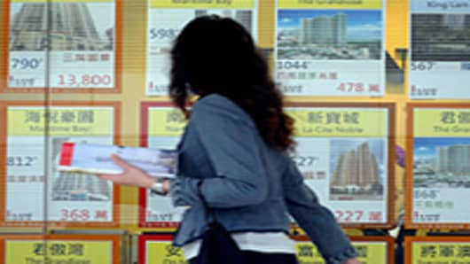 A woman walks past a property agent window in Hong Kong.