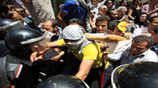 Egyptian opposition activists clash with riot police during a demonstration in front of the Shura Council in Cairo on June 1, 2010 to condemn Israel's deadly raid on a Gaza-bound aid flotilla the day before.