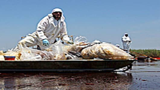 Contract workers from BP ferry oil soaked waste to a pickup point as other workers use skimmers to clean oil from a marsh near Pass a Loutre on June 1, 2010 near Venice, Louisiana. Earlier in the day, U.S. President Barack Obama called the Deepwater Horizon accident the 'greatest environmental disaster of its kind in our history.'
