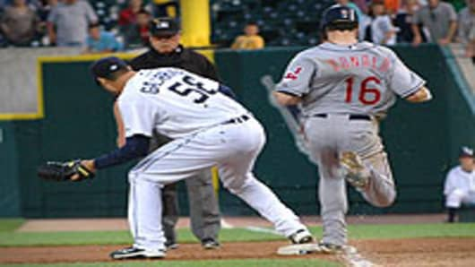 Pitcher Armando Galarraga #58 of the Detroit Tigers covers first base as Jason Donald #16 of the Cleveland Indians steps on the bag while umpire Jim Joyce watches on June 2, 2010 in Detroit, Michigan. Donald was called safe by Joyce, in what would have been the last out of a perfect game thrown by Galarraga.
