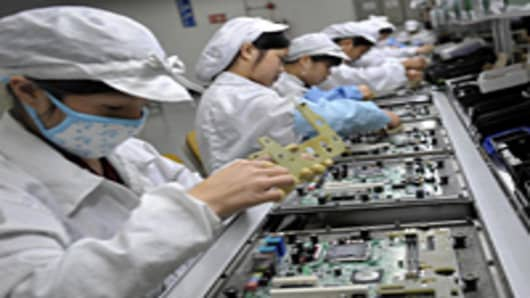 Chinese workers assemble electronic components at the Taiwanese technology giant Foxconn's factory in Shenzhen.