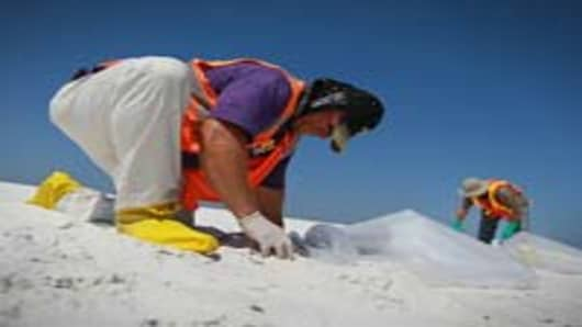 Workers are seen clearing the beach of the oil residue that has washed up on Pensacola Beach from the Deepwater Horizon oil spill in the Gulf of Mexico on June 7, 2010 in Pensacola, Florida. Early reports indicate that BP's latest plan to stem the flow of oil from the site of the Deepwater Horizon incident may be having some success.