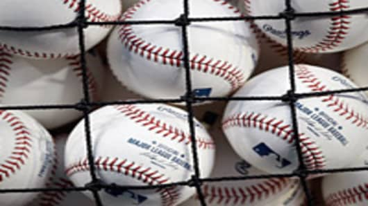 MLB baseballs seen through the netting of a basket