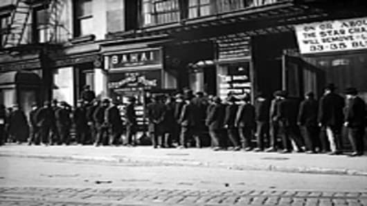 Unemployed men queuing for coffee and bread at a soup kitchen run by the Bahai Fellowship at 203 East 9th Street, New York, circa 1930.