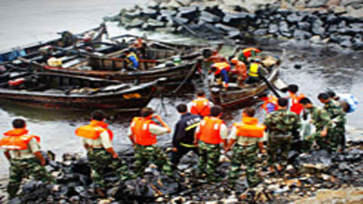 Workers clean up the leaking oil at the polluted sea area on July 20, 2010 in Dalian, Liaoning Province of China. Over 500 fishing boats Monday joined a massive oil spill clean-up operation underway off the coast of Dalian City, three days after pipelines exploded near the city's oil reserve base, one of China's largest.