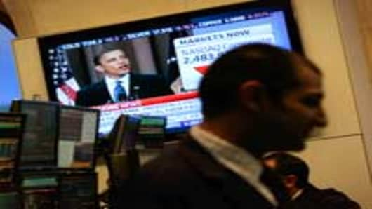 Financial professionals work on the floor of the New York Stock Exchange at midday as President Obama gives a speech about Wall Street financial reform.