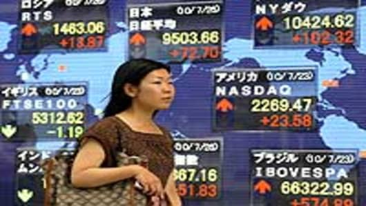 A pedestrian passes before a share prices board in Tokyo, Japan.