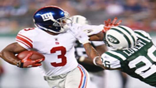 Victor Cruz #3 of the New York Giants breaks a tackle from Dwight Lowery #26 of the New York Gets during the preseason game.