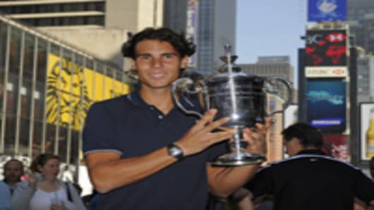Rafael Nadal from Spain poses with his trophy in Times Square September 14, 2010, the morning after winning the Men's Singles Final at the US Open 2010.