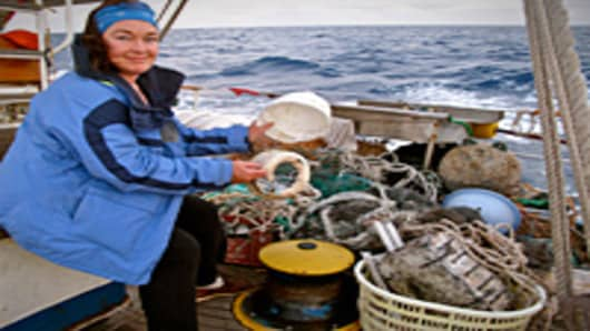 Mary Crowley of Project Kaisei, with some of the plastic trash picked up on a voyage