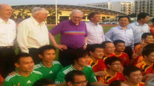 David Sokol, Charlie Munger, Warren Buffett, and Bill Gates pose for photographs with soccer players in Beijing.