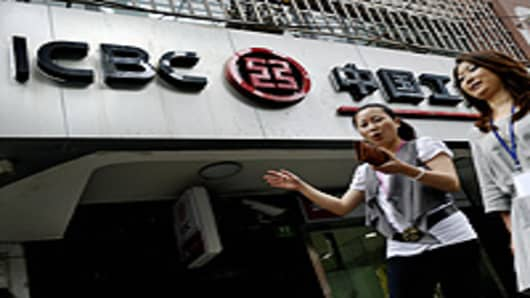 Pedestrians walk past a branch of the Industrial and Commercial Bank of China (ICBC) in Shanghai.