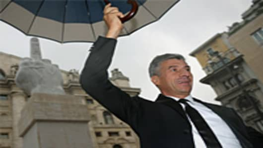 Italian artist Maurizio Cattelan poses near his sculpture depicting the middle-finger gesture during its unveiling in front of Milan stock exchange.