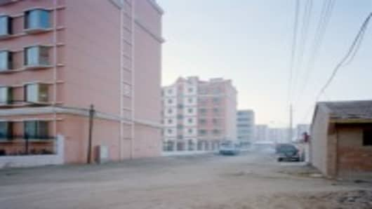 New multistory apartments are build across the street from older single floor homes in western Gansu province, China.