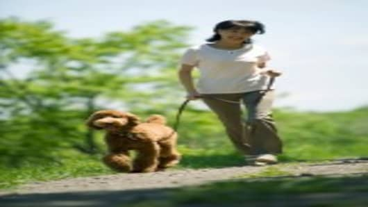 A middle-aged Asian woman walking a dog