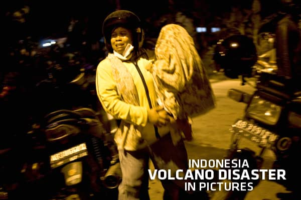 A mother carries her son as she runs following the erupution of Mount Merapi, at Kaliurang village in Sleman, on October 26, 2010 near Yogyakarta, Indonesia.