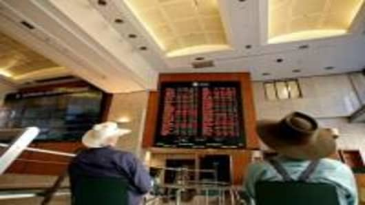 Two men wearing traditional Australian hats look at a board display the ASX index at the Australian Securities Exchange in Sydney, 15 March 2007.