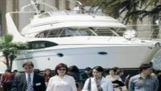 Visitors walk past a yacht displayed at the International Boat Show in Shanghai, 08 April 2005.