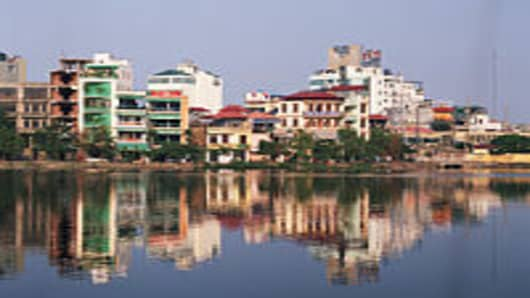 Vietnam, Hanoi skyline with reflection in river.
