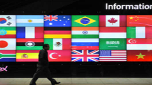 A man walks in front of a screen showing flags of the participating nations for the upcoming G20 Summit at its venue in Seoul on November 4, 2010.