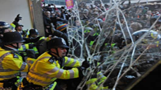 Police officers hold back demonstrators trying to gain entry to 30 Millbank, the headquarters of Britain's Conservative Party, during a protest in central London.