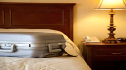 Suitcase on bed in hotel room.