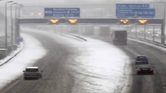 Cars and lorries are driven along the snow covered M25 in Kent, in south-east England on December 1, 2010. Britain's transport links with the rest of the world were disrupted by the early winter snowfall as key airports closed Wednesday and international Eurostar train services were cut. London Gatwick Airport, Europe's eighth busiest passenger air hub, was closed until at least 6:00am (0600 GMT) Thursday as staff worked on clearing the two runways.