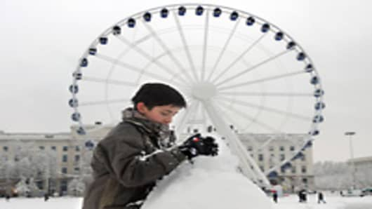 A child sets a snowman in front of a ferrywheel place Bellecour, on December 1, 2010 in Lyon. Snow and freezing temperatures forced French aviation authorities to cancel 116 flights from Lyon airport today and brought 10,000 trucks to a halt, officials said.