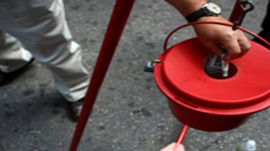 A pedestrian donates a dollar to the Salvation Army bell-ringer stand.