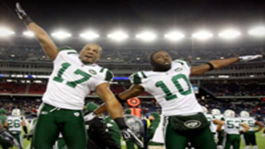 Braylon Edwards #17 and Santonio Holmes #10 of the New York Jets celebrate on their way to defeating the New England Patriots.