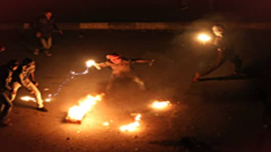 Egyptian demonstrators demanding the ouster of President Hosni Mubarak throw fire bombs at police in Suez on January 27, 2011.