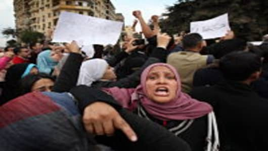 A woman shouts as she blocks the entry of army tanks to Tahrir Square on January 30, 2011 in Cairo, Egypt. Cairo remained in a state of flux and marchers continued to protest in the streets and defy curfew, demanding the resignation of Egyptian president Hosni Mubarek. As President Mubarak struggles to regain control after five days of protests he has appointed Omar Suleiman as vice-president. The present death toll stands at 100 and up to 2,000 people are thought to have been injured during the