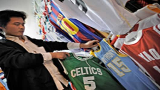 A man arranging fake NBA jerseys on sale at a market.