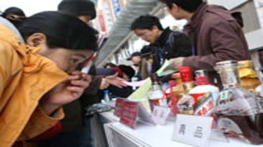 Customers learn to distinguish alcohol products from the fake ones during an event held by the General Administration of Quality Supervision, Inspection and Quarantine, to mark the World Consumer Rights Day at the Wangfujing Shopping Street in Beijing, China.