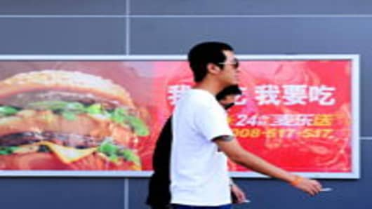 Two Chinese men walk past a billboard advertising US fast-food giant McDonald's, in Yichang, central China's Hubei province.