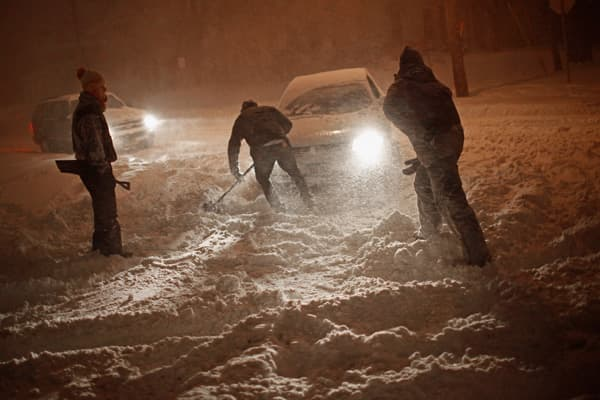 A group of men work to dig a path for their car to drive through a heavy snowfall late night February 1, 2011 in Iowa City, Iowa.