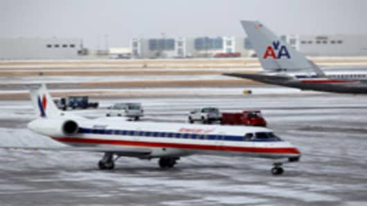An American Airlines jet taxis to a gate after an overnight ice storm forced the closure of DFW International Airport on February 1, 2011 in Dallas, Texas.