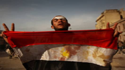 An anti-government protestor holds a blooded Egyptian flag in Tahrir Square on February 3, 2011 in Cairo, Egypt.