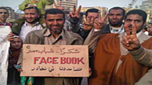 """Man carrying Facebook sign, reading """"Thank you youth of Egypt"""" and """"We are holding our ground. We are not going to leave"""" at bottom."""