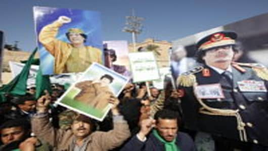 "Supporters of Libyan leader Moamer Kadhafi hold his pictures as they take part in a pro-government rally in Tripoli on February 17, 2011 as the country faced a nationwide ""Day of Anger"" called by opposition cyber activists."