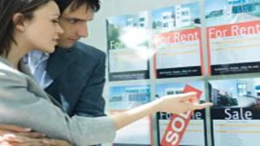 Couple looking at properties in window of real estate agency.