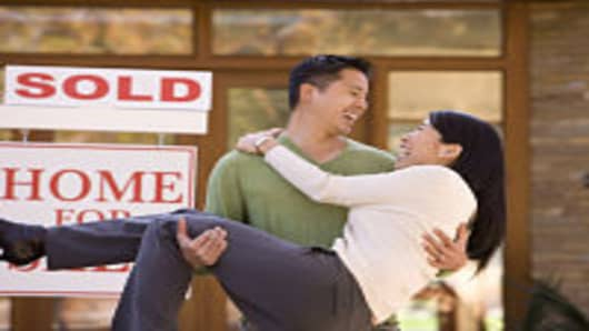 Asian Couple Embracing in Front of New Home