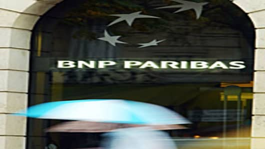 Pedestrians walk past the BNP Parisbas headquarters in Paris.