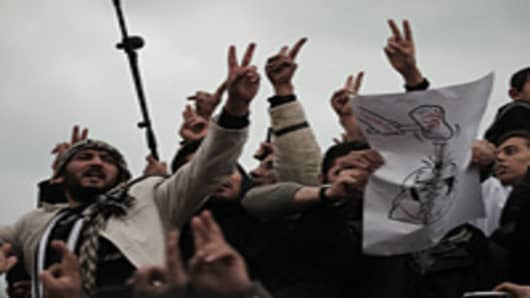 Libyans shout slogans against Libyan leader Moamer Kadhafi while holding a cartoon depicting Kadhafi being hit with a hammer symbolising 'the people's will'.