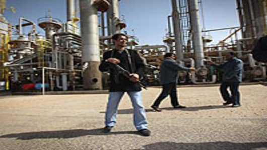 A rebel militiaman stands guard at a Libyan oil refinery in rebel-held territory on February 27, 2011 in Al Brega, Libya. The opposition leadership has stressed that oil faciities in areas under its control are safe, despite the conflict roiling the country.
